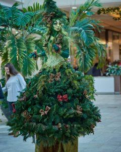 femme sur échasse déguisée en sapin de Noël magique | Concepts d'arrivée du père Noël à l'ère du covid