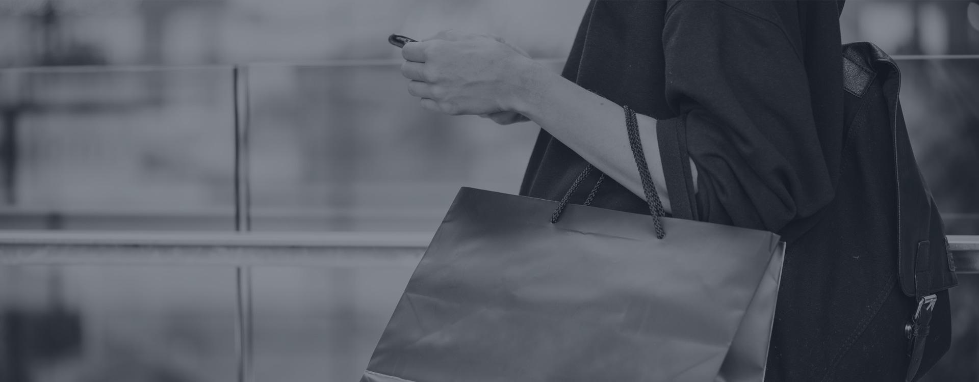 Femme portant des sacs de magasinage regardant son cellulaire