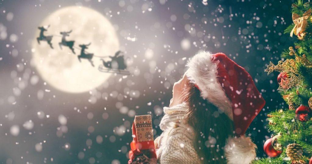 Fillette avec un cadeau qui admire le traîneau du père Noël dans le ciel - Comment réinventer la rencontre avec le père Noël - Audace