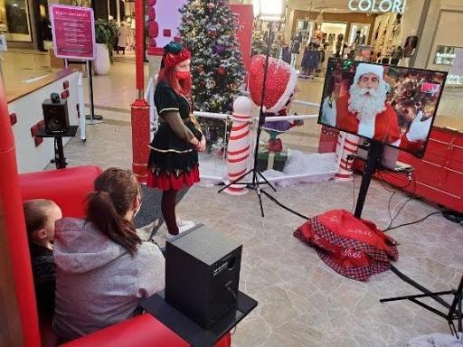 Royaume du Père Noël - famille assise sur le trône, discutant avec le Père Noël par vidéoconférence sous le regard attentif d'une lutine masquée   Audace & Co.
